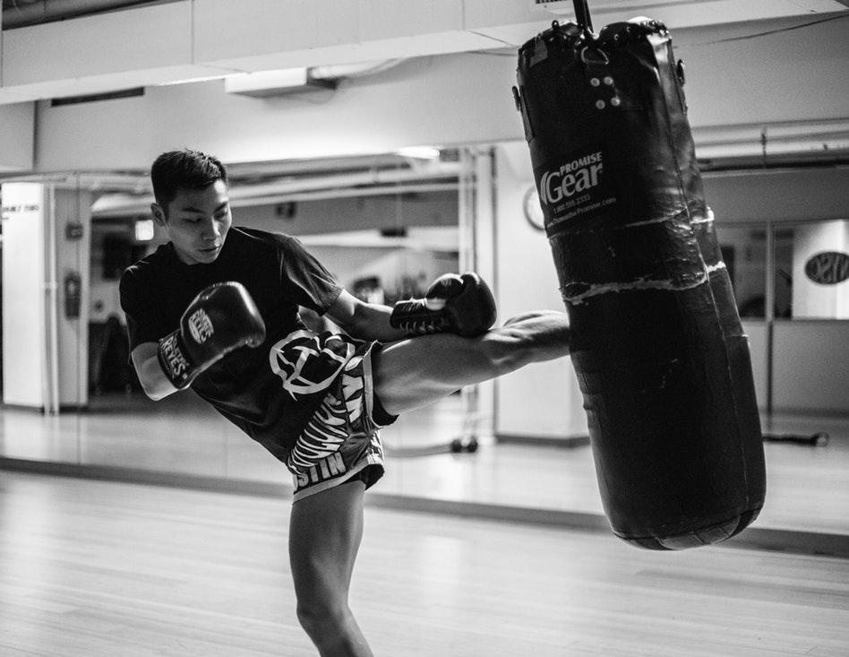 Man kicking a punching bag